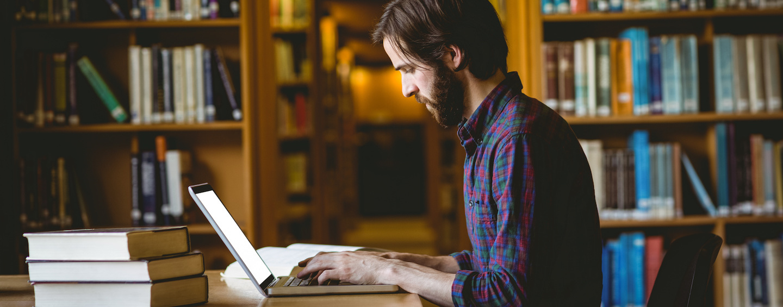 Hombre sentado en una biblioteca escribiendo en un computador