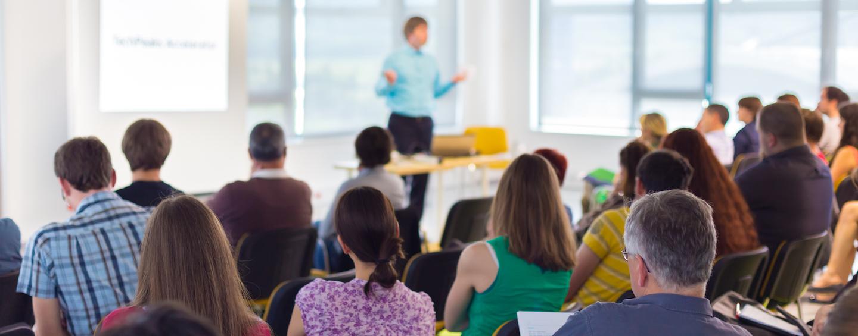 Orador en una sala frente al público.