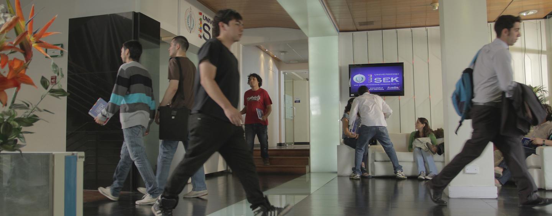 Personas caminando en el hall de una sede universitaria.