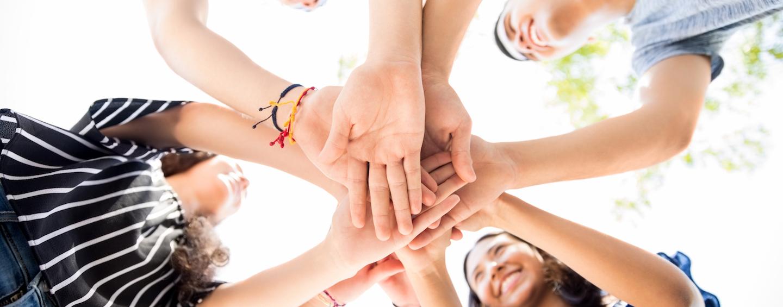 Grupo de personas colocando las manos una sobre otra.